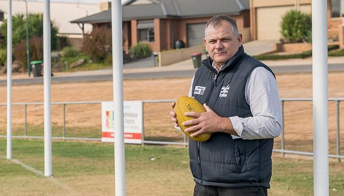 Darryl Wilson holding football standing on football oval