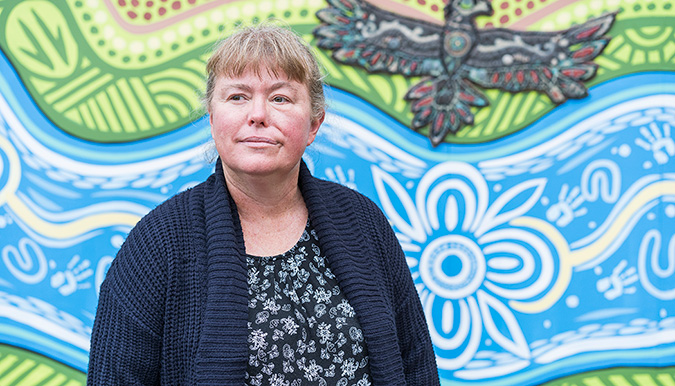 Donna Matthews standing in front of colourful mural of a river and bird