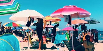 People under colourful beach umbrellas on a sunny, sandy beach
