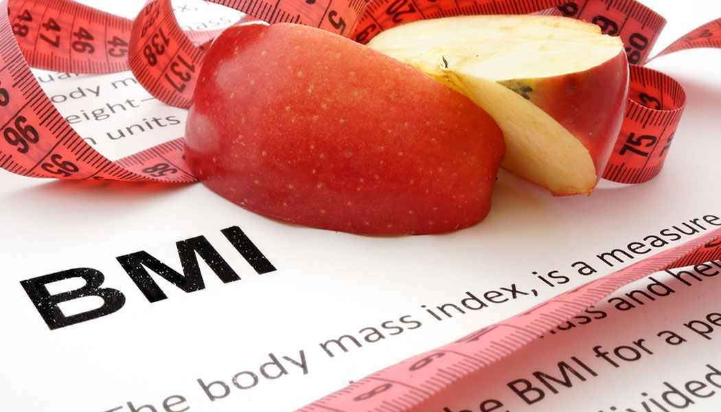 A written description of body mass index with a sliced red apple and tape measure in the background