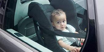 Toddler sitting in a child seat in a car
