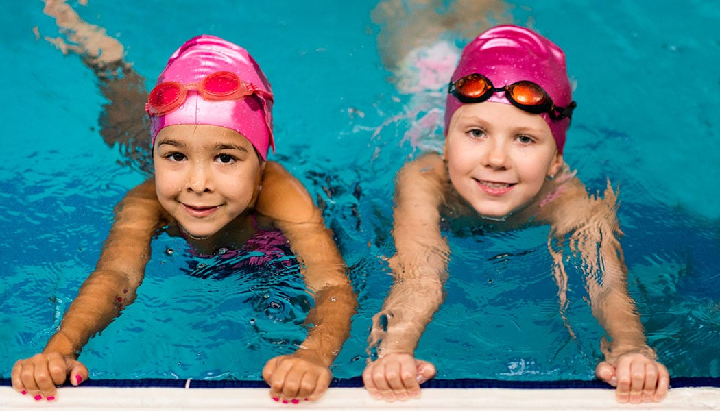 two girls swimming in pool, both wearing pink swimming caps and goggles