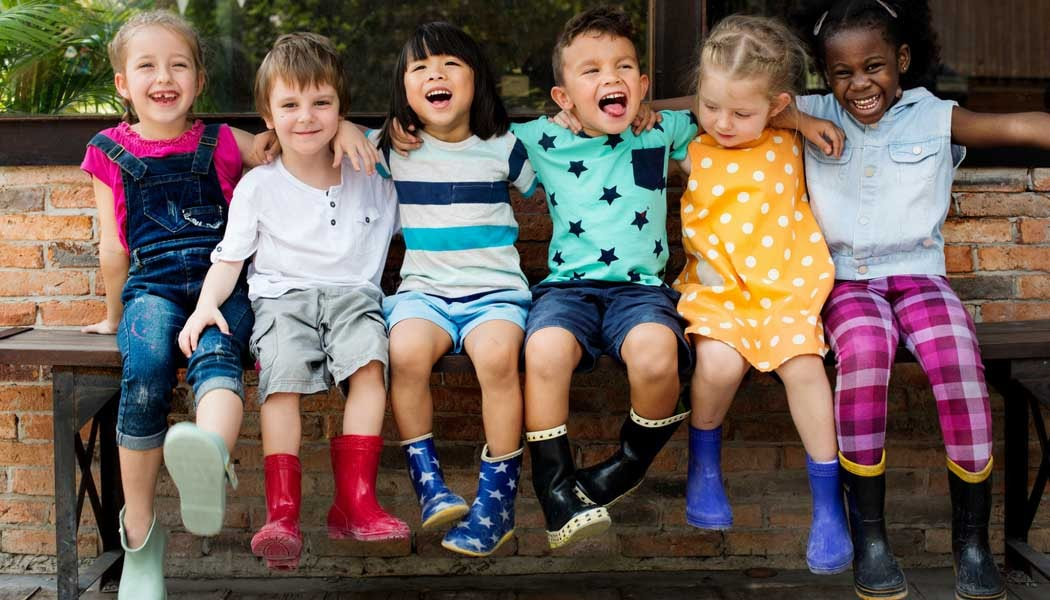 6 young children sitting on a bench smiling and pulling funny faces