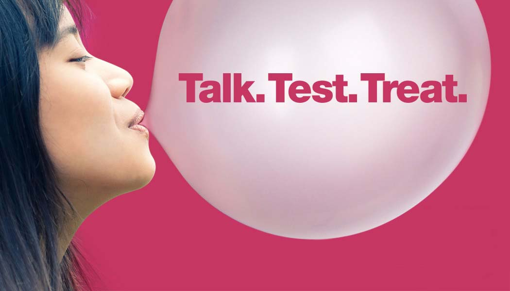 Woman blowing bubble with the words - Talk. Test. Treat. Inside Bubble