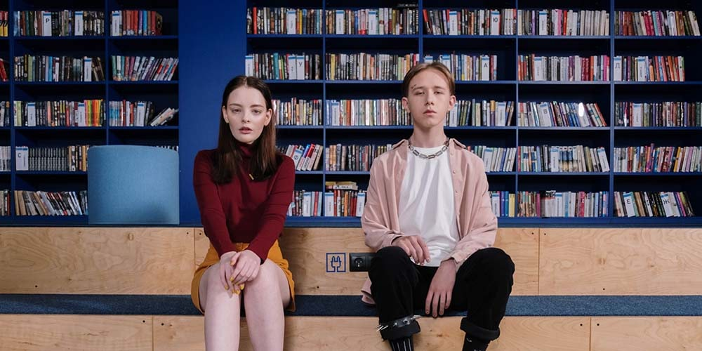 Two teenagers sitting in library