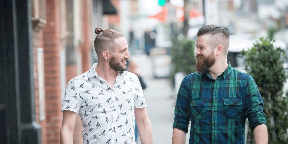 Two men walking in the street and smiling at each other
