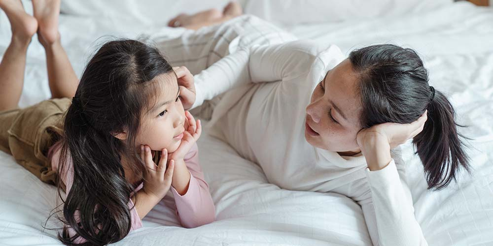 Mum and young daughter talking on bed