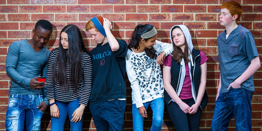 Group of teenagers against a brick wall