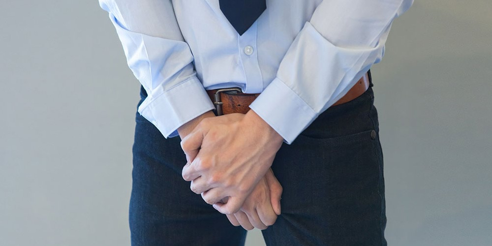 Fully dressed man with hands covering his genital area
