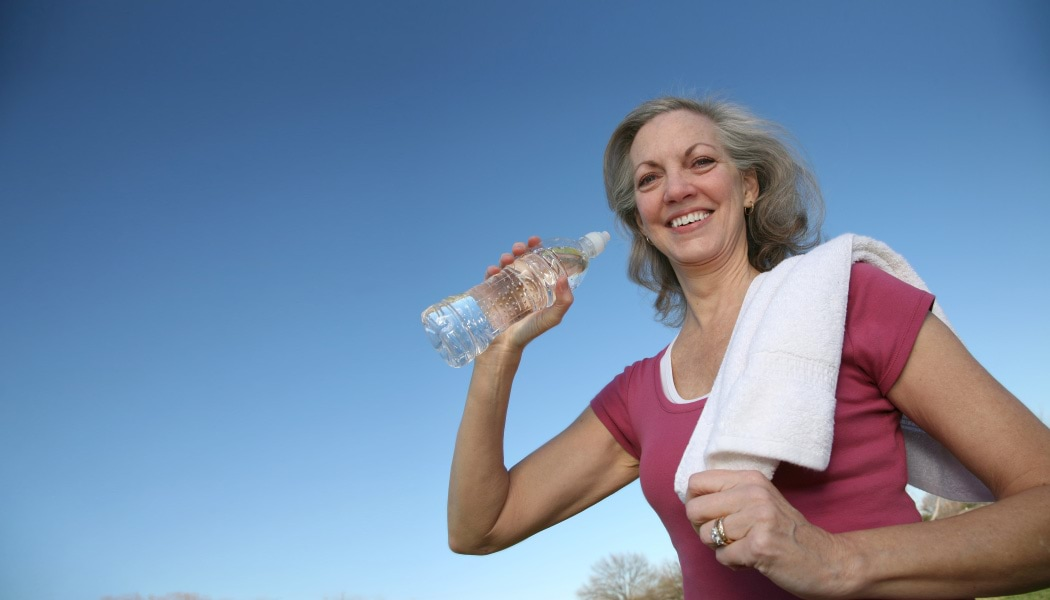 Woman exercising with water bottle