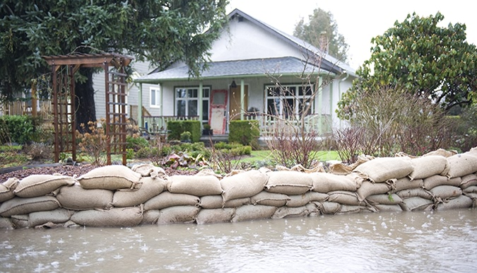 Sand bags holding back flood waters at the front of a house