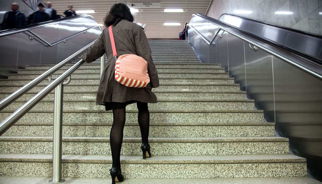 Woman taking stairs with escalators either side